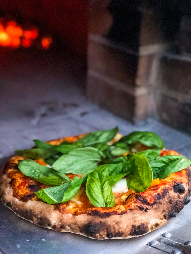 Homemade pizza in the pizza oven by A Lady Goes West