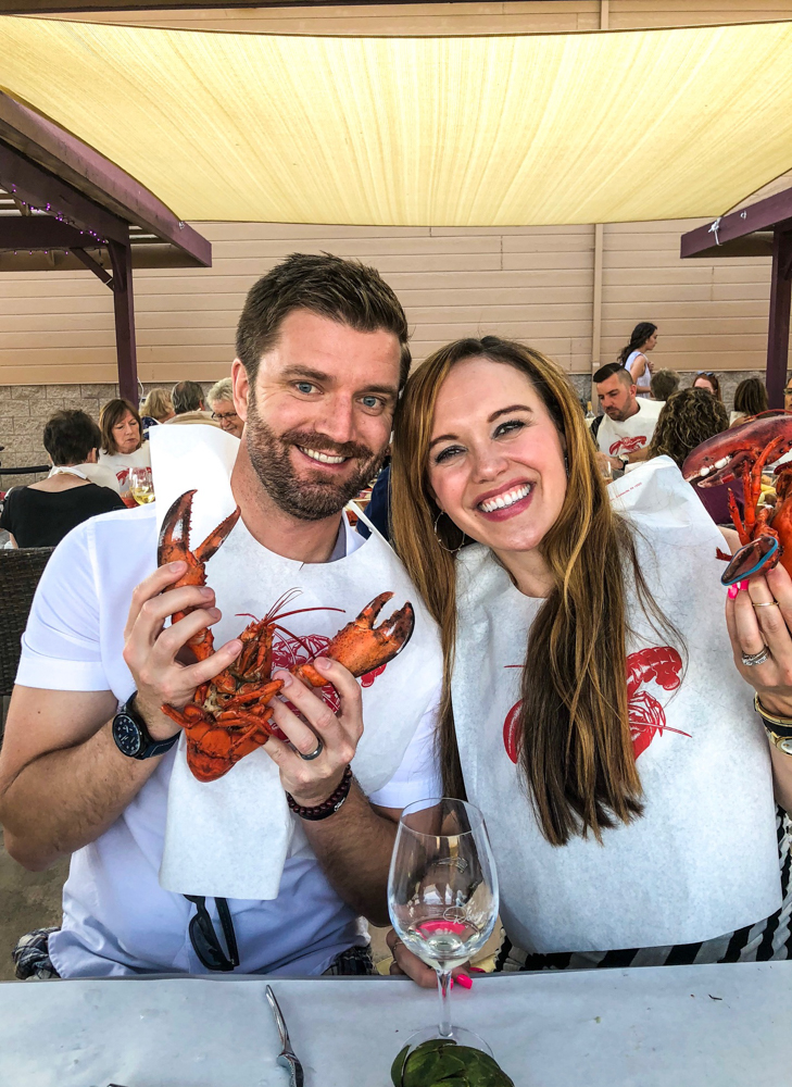 Ashley and Dave at a table of food at the Livermore lobster bake with wine fave by A Lady Goes West
