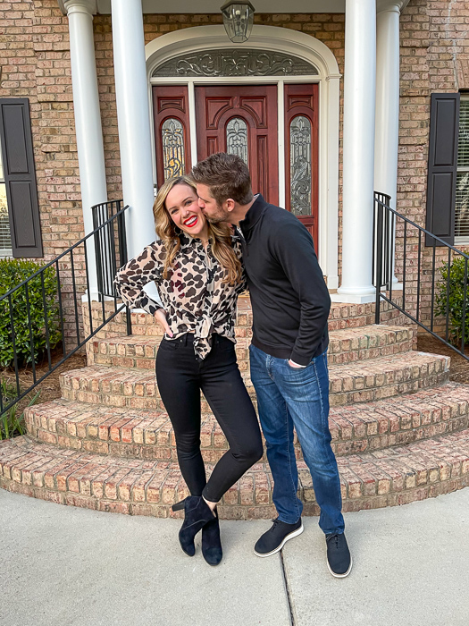 Ashley and Dave outside brick house March 2021 by A Lady Goes West